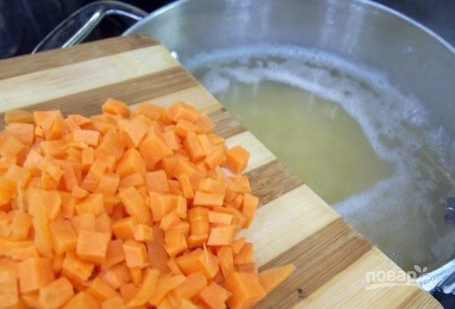 Очистите, промойте и нарежьте мелкими кубиками морковь. Добавьте её в суп.