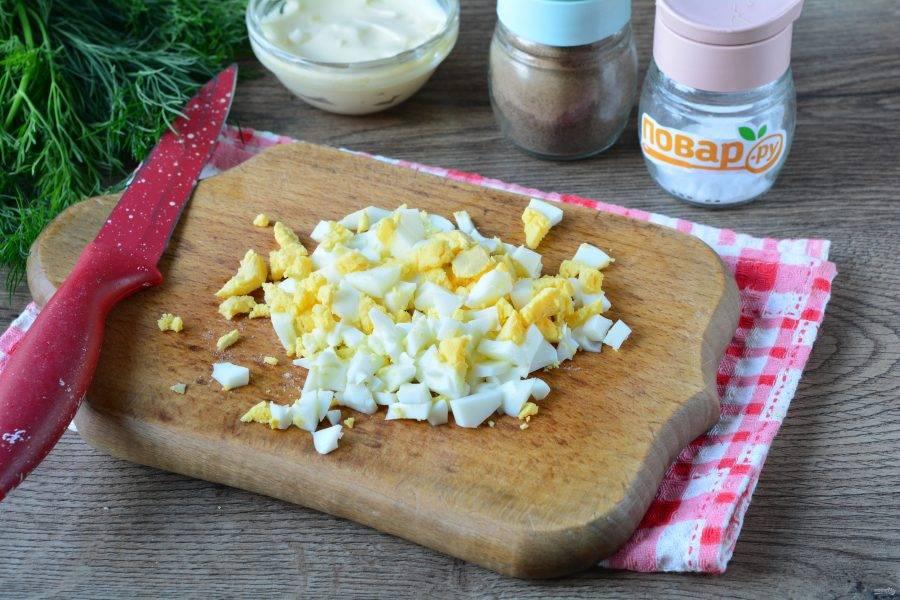 Сваренные вкрутую яйца нарежьте кубиками для салата.