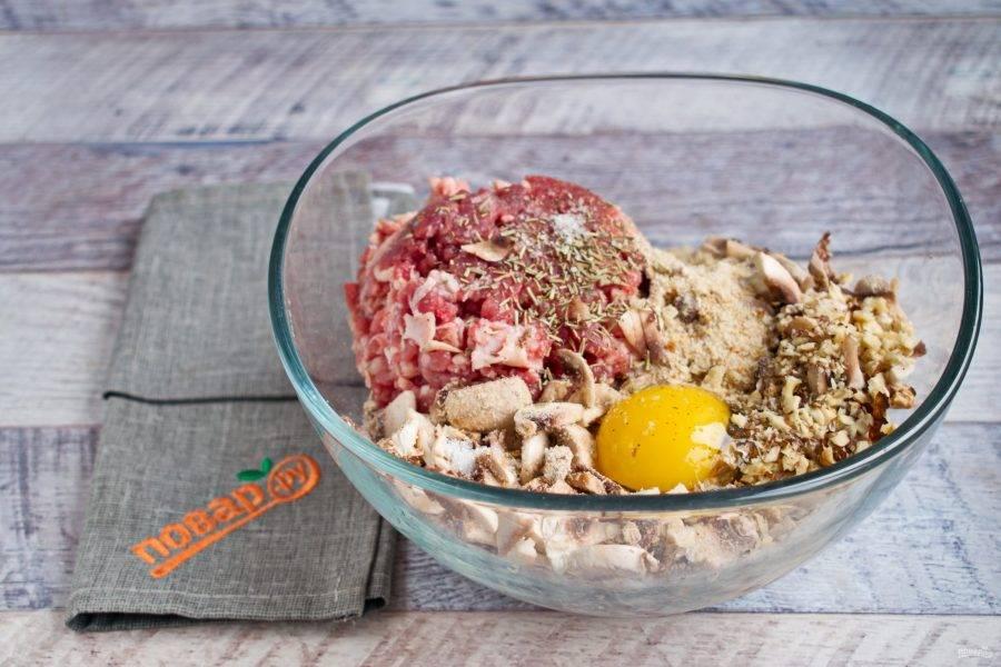 В миске соедините говяжий фарш, яйцо, измельченные орехи, панировочные сухари, мелко нарезанные грибы, соль и перец по вкусу. Перемешайте до однородности.