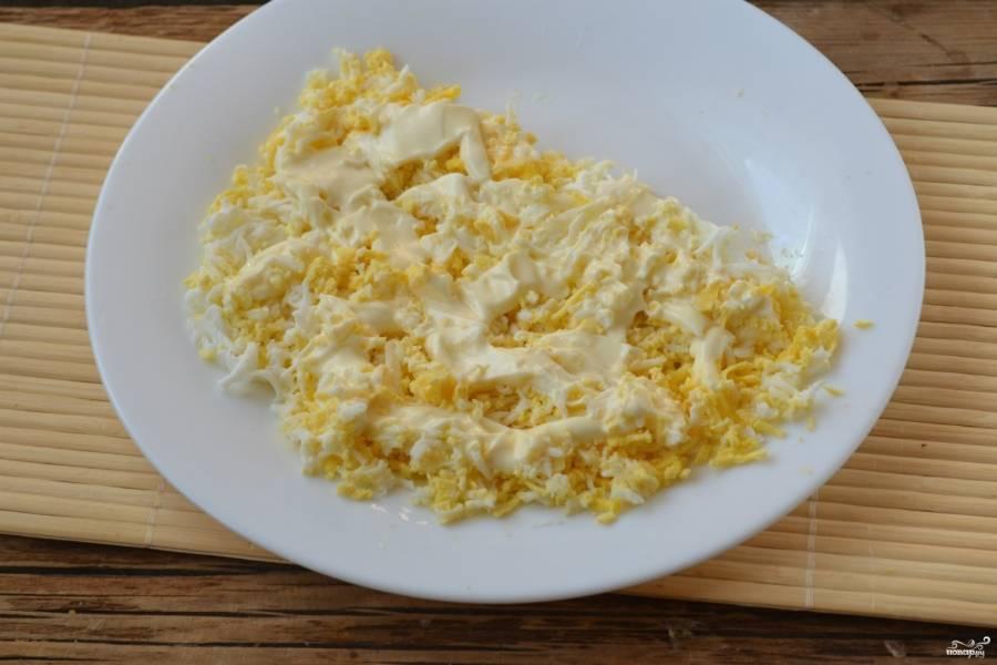 Салат выкладывайте в форме полукруга. Первым слоем натрите яйца, отложив белок одного яйца. Он нам ещё понадобится для украшения. Смажьте первый слой майонезом.