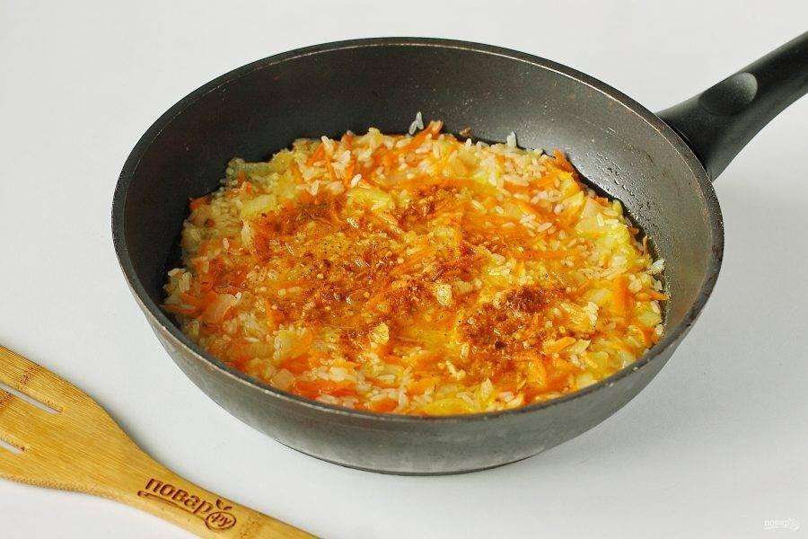 Налейте стакан горячей воды или мясного бульона. Добавьте по вкусу соль и специи (у меня для курицы). Перемешайте и на небольшом огне под крышкой готовьте до тех пор, пока рис полностью не приготовится. В процессе по мере впитывания жидкости необходимо ее подливать, и перемешивать рис ложкой или лопаткой.