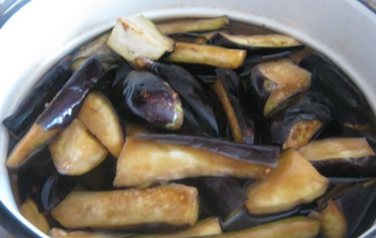 Через 2 часа тщательно промойте баклажаны. Переложите их в кастрюлю, залейте водой и доведите до кипения, после чего варите 5 минут.