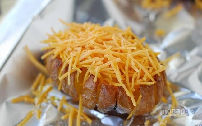 6. Достаньте картофель, снова полейте его маслом, присыпьте тертым сыром и запекайте еще минут 25-30.