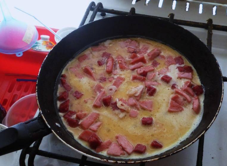 Теперь заливаем на сковороду приготовленную яичную смесь, накрываем крышкой и готовим омлет до полного его застывания.