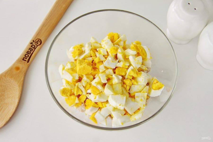 Добавьте нарезанные кубиками вареные яйца.