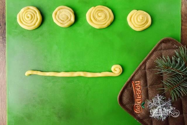 Белое тесто разделите на 16 равных частей. Скатайте жгутики и сверните их спиралью.