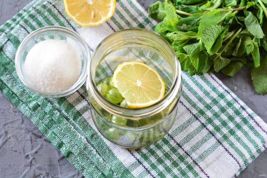 На дно простерилизованной банки выложите вымытый крыжовник и кусочки лимона.