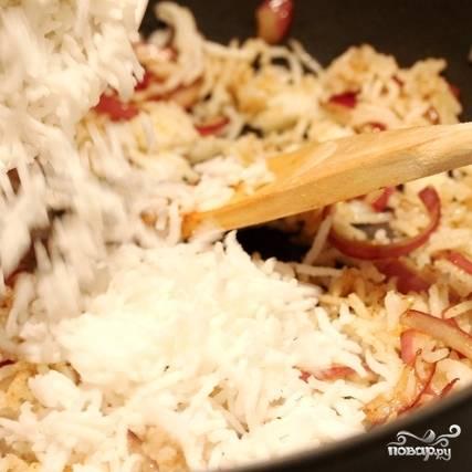 Затем добавляем в сковороду уже готовый отварной рис.