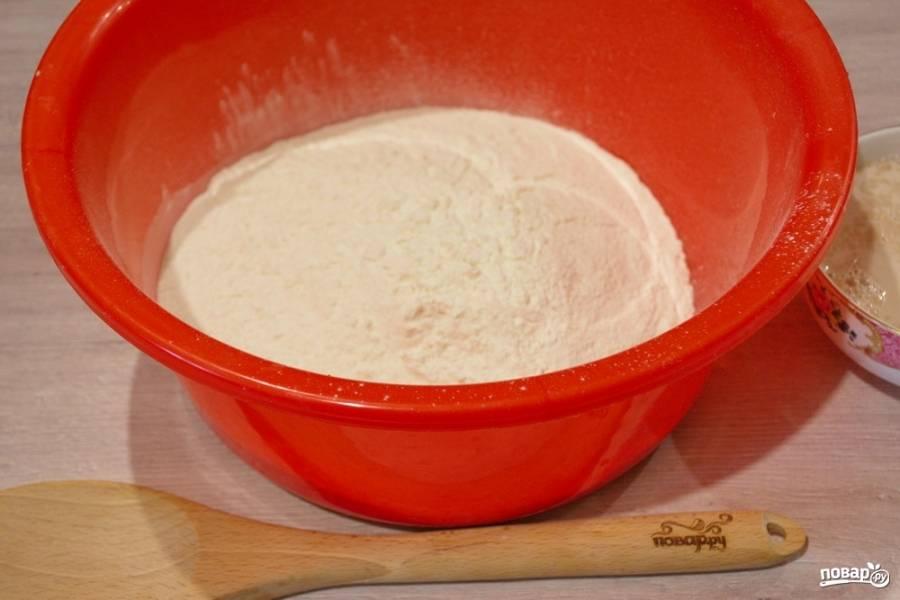 2. Муку двух видов необходимо просеять. Поместите в миску для замеса теста (миска должна быть глубокой). В центре сделайте воронку. Введите дрожжи. Замесите тесто.