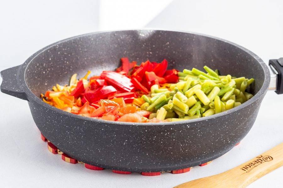 Затем добавьте нарезанный соломкой перец, стручковую фасоль и нарезанный кубиками помидор. Аккуратно перемешайте и готовьте 5-7 минут на среднем огне. Затем выключите плиту и дождитесь готовности желудков.