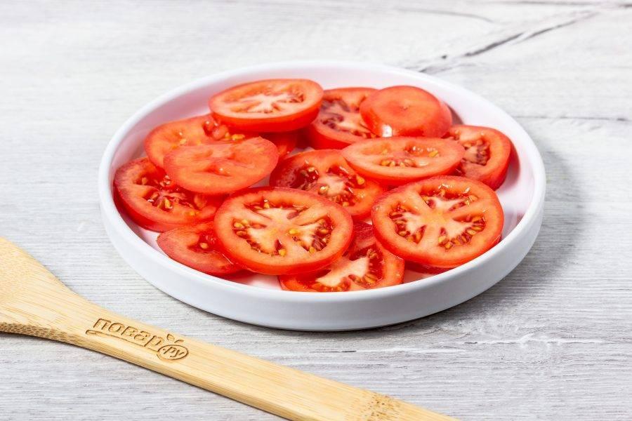 Помидоры нарежьте кружочками и выложите на плоское блюдо.