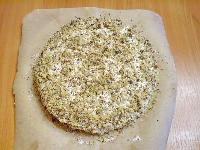 15. Посыпаем орехами. И с двух сторон вытягиваем бумагу. Отправляем тортик в холодильник на 2 часа.