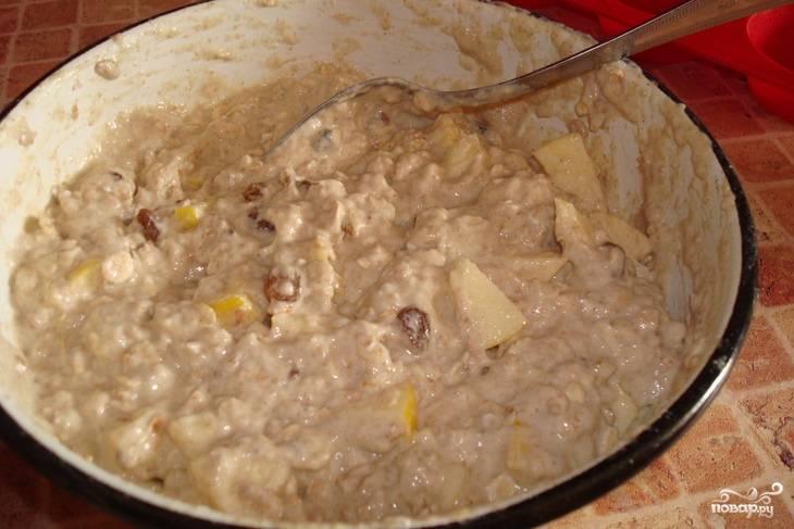 Для приготовления теста залейте молотые овсяные хлопья соком и дайте постоять 10 минут. Затем положите туда яблоки и изюм. Муку просейте, погасите соду уксусом и всё хорошо перемешайте. В тесто можно добавить ложку растительного масла.