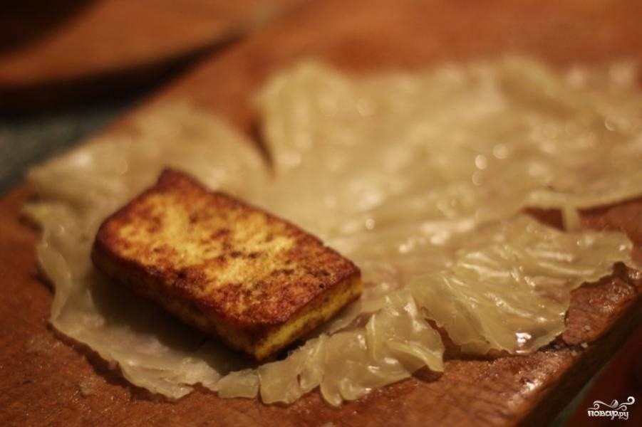 Сваренный кочан разделить на отдельные листья, слегка отбить каждый лист в местах сгиба и завернуть в него обжаренный сыр.