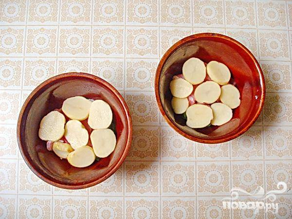 3.Очищаем от шкурки молодой картофель, кружочками его нарезаем, в теплой воде промываем, и обсушиваем. Укладываем картофель сверху на мясо, немного присолим.