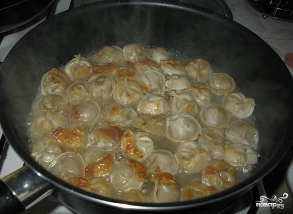 4. Чтобы замороженные пельмешки хорошо проготовились, влейте на сковороду горячую воду (так, чтобы она покрыла их). Оставьте на среднем огне до тех пор, пока вода полностью не выкипит. Перед подачей можно дополнить маслом, щепоткой перца, зеленью или сметаной. Приятного аппетита!