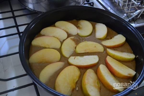 4. Вылейте половину теста в смазанную маслом или застеленную пергаментом форму. Распределите нарезанные ломтиками яблоки.