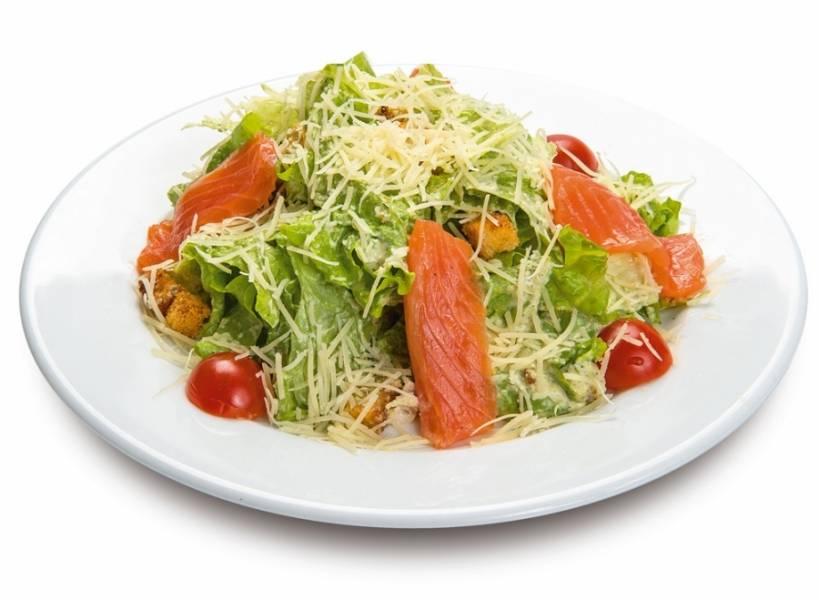 Листья салата заправить частью соуса и половиной пармезана, перемешать. Выложить кусочки рыбы, крутоны и полить остатками соуса. Посыпать тертым пармезаном. По желанию украсить половинками черри. Приятного аппетита!
