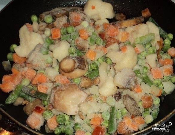 2. Первым делом отправьте на огонь кастрюлю с водой и доведите до кипения. На сковороду налейте немного растительного масла и выложите смесь овощей и грибов, начните обжаривать.