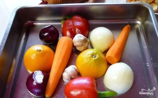 После этого все овощи и апельсин помойте. Всё, что необходимо, очистите от кожуры. Уложите продукты на противень.