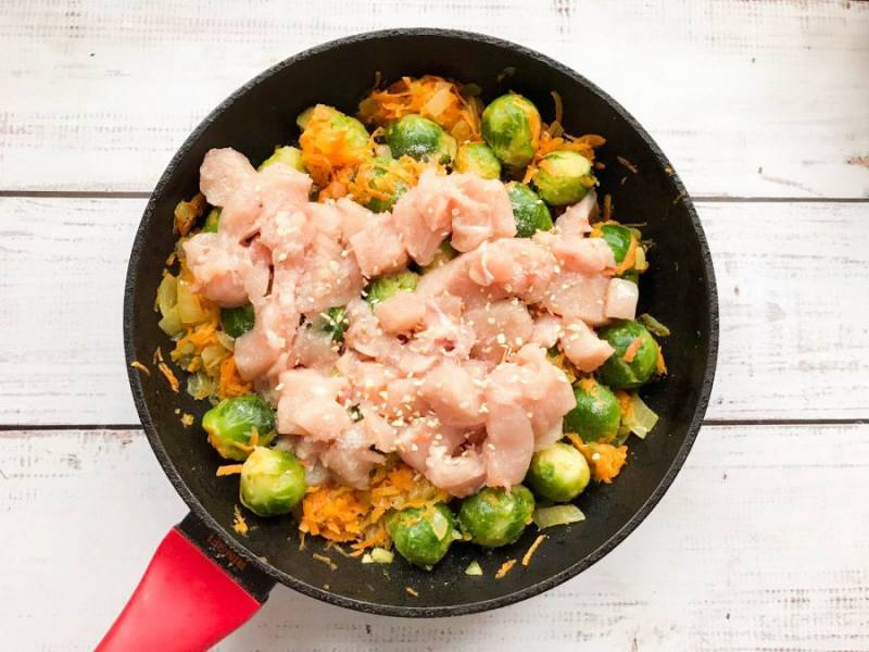 Курицу хорошо помойте под чистой водой, обсушите бумажным полотенцем, нарежьте небольшими кусочками, выложите к овощам, посолите, добавьте специи и тушите на среднем огне 20-25 минут.