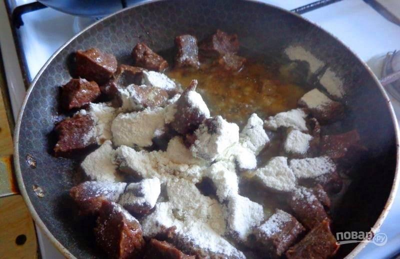 Когда мясо выделит сок, а половина этой жидкости выкипит, добавьте муку, перемешайте и обжаривайте еще 1-2 минуты.