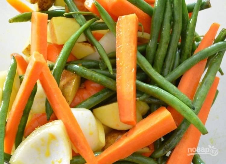 1.Очистите овощи, нарежьте лук и картофель крупными кусочками, разрежьте большую морковь вдоль на клинья. Смешайте горчицу, мед, яблочный уксус и оливковое масло, добавьте смесь к овощам и перемешайте.
