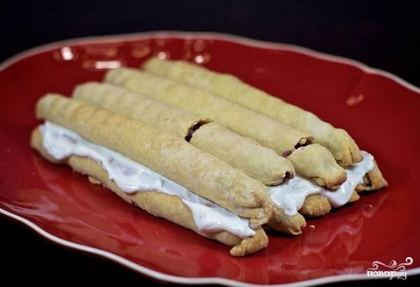 """8. Выложите 5 полосок на тарелку и промажьте кремом. Сверху выложите 4 штучки. Торт """"Вишня в снегу"""" в домашних условиях будет иметь форму домика. Так повторяйте слои, уменьшая количество трубочек и переслаивая их кремом."""