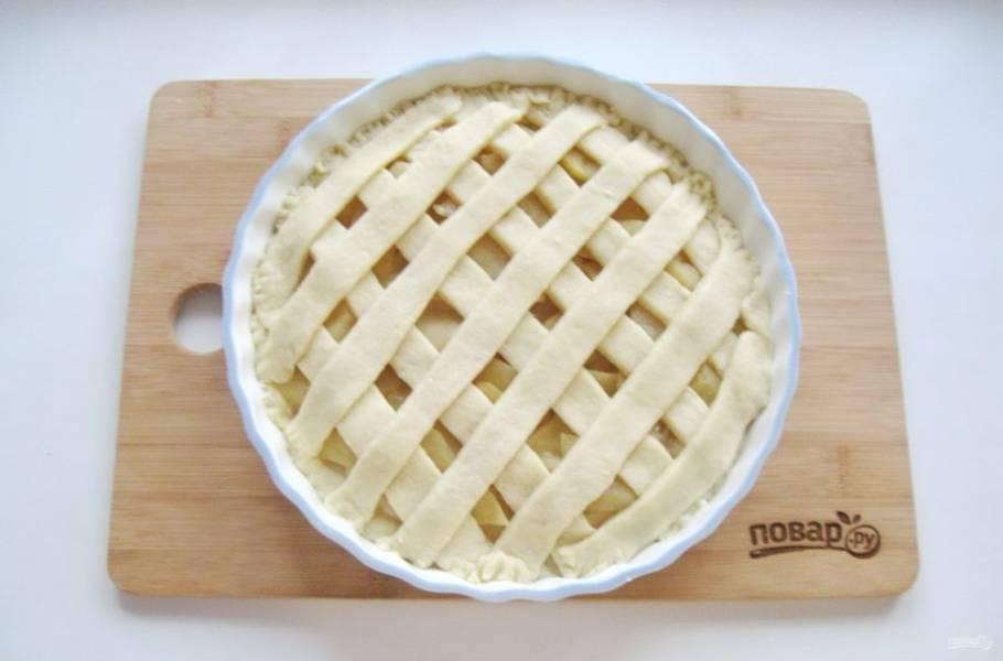 Вторую часть теста раскатайте в пласт, который нарежьте полосками шириной 1,5-2 см. Выложите полоски решеткой на яблоки.