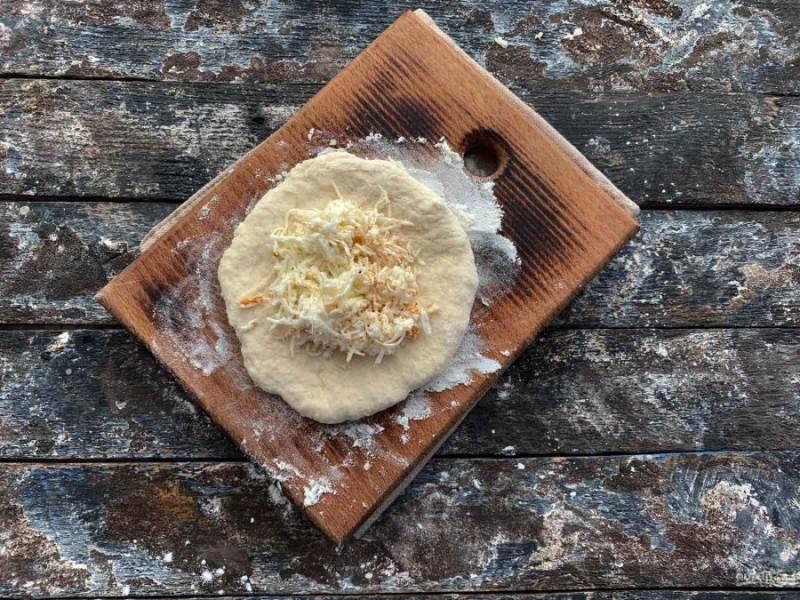 Тесто разделите на несколько частей. Каждую часть раскатайте в небольшую лепешку, в центр выложите начинку из сыра.