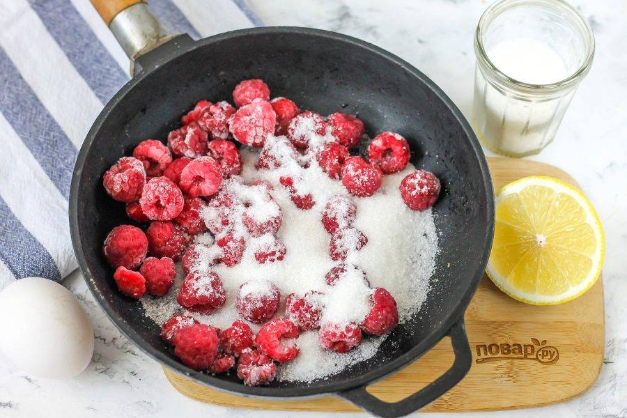 Выложите малину в емкость с антипригарным дном, засыпьте сахаром и поместите емкость на плиту.