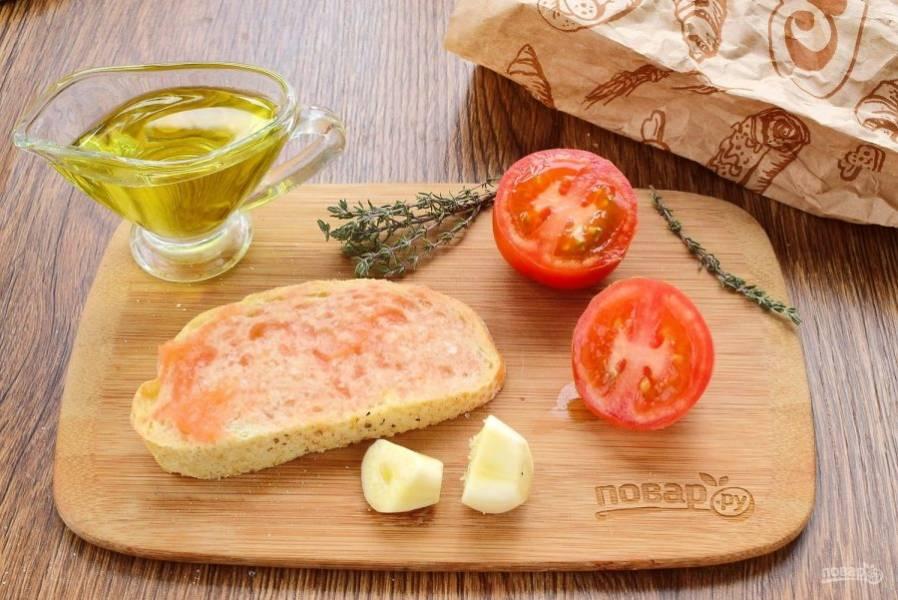 Чеснок и помидоры разрежьте пополам. Натрите хлеб чесноком, смажьте оливковым маслом и натрите мякотью помидора.
