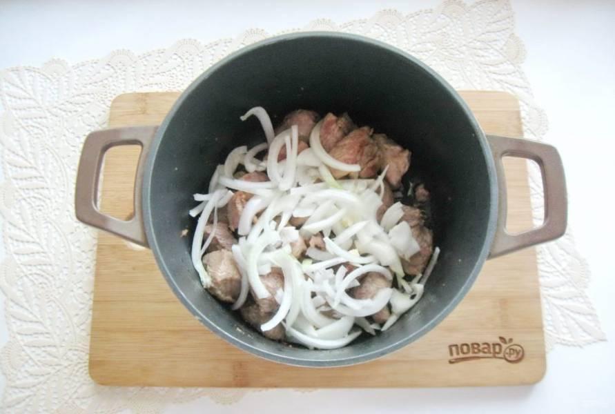 Лук очистите, помойте и нарежьте полукольцами. Выложите в кастрюлю с мясом.