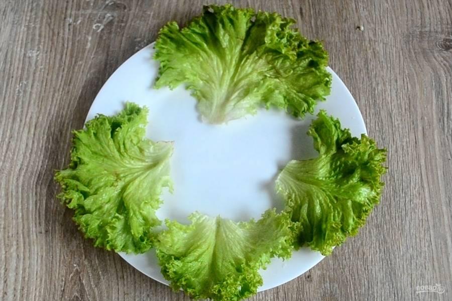 На большую плоскую тарелку выложите листья салата (не забудьте его предварительно ополоснуть и высушить).