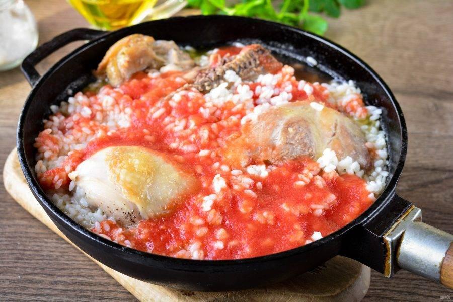 Затем влейте томатный соус, перемешайте и тушите под крышкой еще 10-12 минут до полной готовности риса и мяса. Поперчите по вкусу.