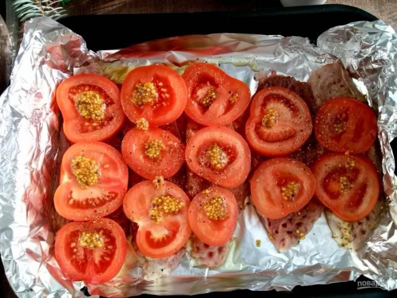 Разогрейте духовку до 180 градусов. Форму для запекания застелите фольгой и смажьте оливковым маслом. Помидоры нарежьте ломтиками толщиной в 1 см и положите поверх мяса, смажьте горчицей.