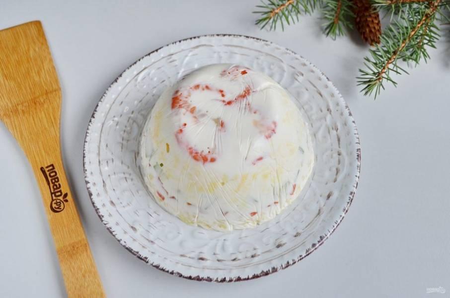Застывший салат переверните на тарелку, удалите осторожно пищевую пленку. Украсьте и подайте салат.