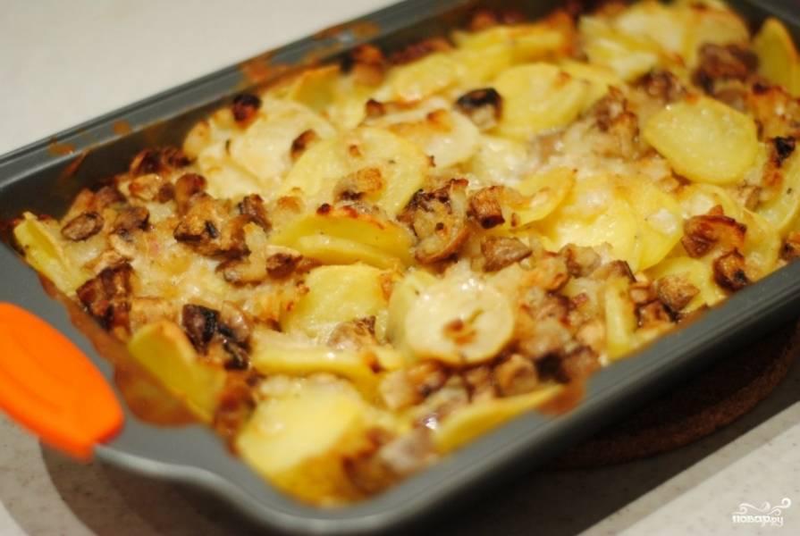 Картофель выложите в форму для запекания. Добавьте грибы, лук, специи и сметану и все хорошенько перемешайте. Можно также присыпать сыром. Поставьте форму в разогретую до 180 градусов духовку и запекайте 40 минут.