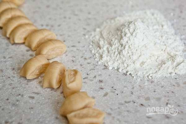 7. Готовое тесто раскатайте в несколько колбасок. Каждую нарежьте кусочками. Добавляйте по мере необходимости муку.