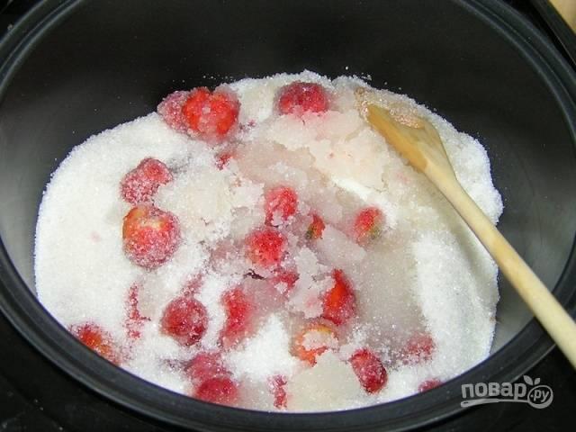 Выложите ягоды в чашу мультиварки. Засыпьте к ним сахар. Спустя 10-15 минут пойдёт сок, тогда добавьте воду.