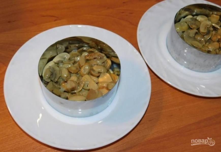 Выложите обжаренные грибы первым слоем салата. Смажьте майонезом.