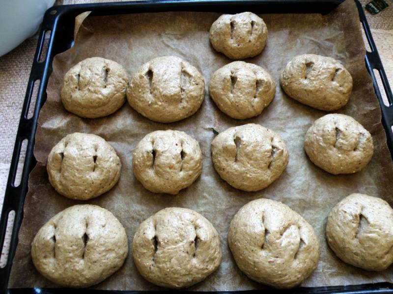 Разделываю тесто на кусочки размером со среднее яблоко. Подкатываю в шарики, кладу на лист, покрытый ковриком для выпечки и делаю пару насечек на каждой булочке. Прикрываю пищевой пленкой и даю расстояться вдвое.