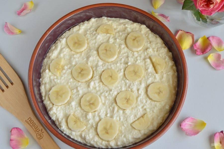 Смажьте растительным маслом огнеупорную форму, выложите и разровняйте творожную массу. Сверху положите кружочки бананов.