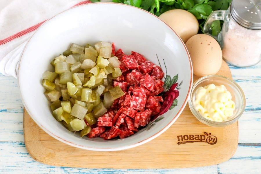 Колбасу очистите от оболочки, нарежьте кубиками и высыпьте в миску или салатник. Соленые, квашеные или маринованные огурцы нарежьте такими же кубиками и оставьте нарезку на 5 минут на досочке, чтобы из нее выделился сок. Затем отожмите и добавьте к колбасе.