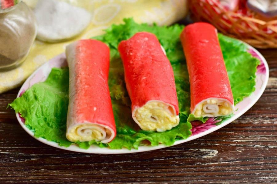 Выложите фаршированные крабовые палочки на блюдо. Для более эффектной подачи используйте листья салата.