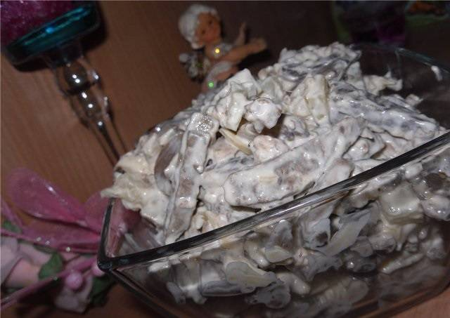 6. Очистите и пропустите через пресс чеснок. Добавьте его в майонез или в сметану (в зависимости от того, что именно вы используете в качестве заправки).  Выложите в салатник, как следует перемешайте и отправьте салат в холодильник примерно на 1 час. Перед подачей добавьте зелень (при желании).
