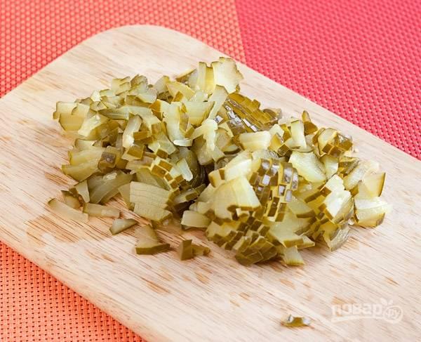 Нарежьте солёные огурцы.