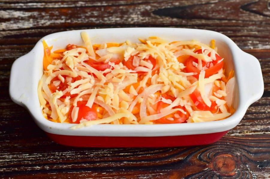 Выложите на тыкву сверху лук, затем помидоры. Посыпьте массу тертым твердым сыром.