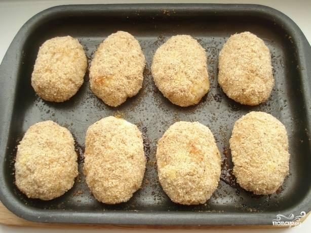 Формируем из массы овальной формы котлеты. Обваливаем каждую в панировочных сухарях. Выкладываем куриные котлетки на смазанный сливочным маслом противень. Ставим в духовку на 40 минут. Температуру выставляем 180 градусов.