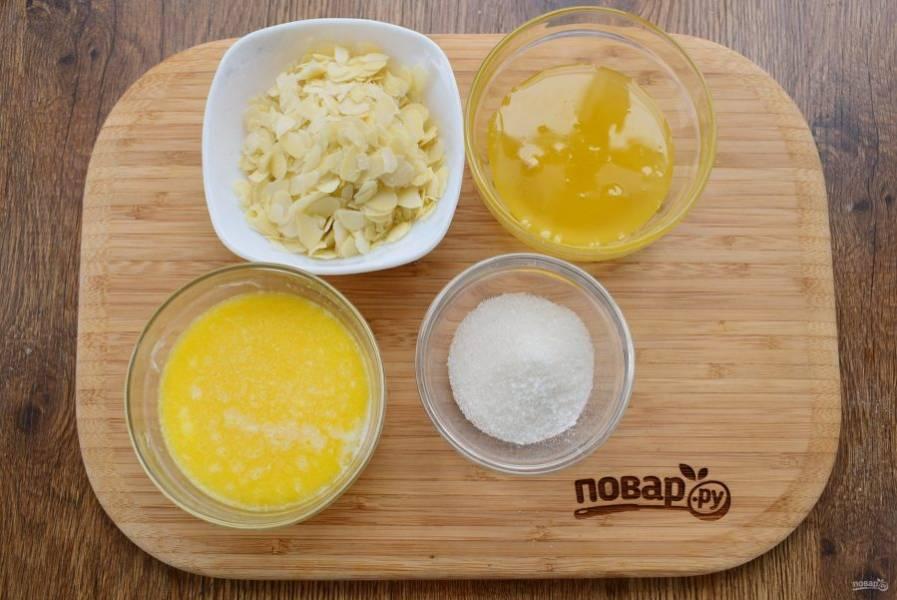 Подготовьте необходимые продукты для медово-миндальной заливки. В кастрюльке с толстым дном или сотейнике соедините мед, сливочное масло, сахар и ванилин, доведите до кипения, варите на медленном огне в течение 1 минуты, добавьте миндальные хлопья (или рубленый миндаль) и перемешайте. Остудите до комнатной температуры.